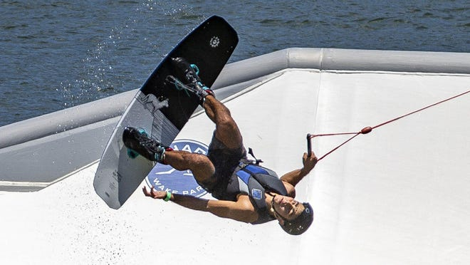 A wakeboarder performs a trick on a cable line Monday at Shark Wake Park in Okeeheelee Park off of Forest Hill Boulevard east of Florida's Turnpike. The cable pull reopened and runs from noon till 7 p.m. except Tuesday,  when it is closed. The obstacle course remains closed.