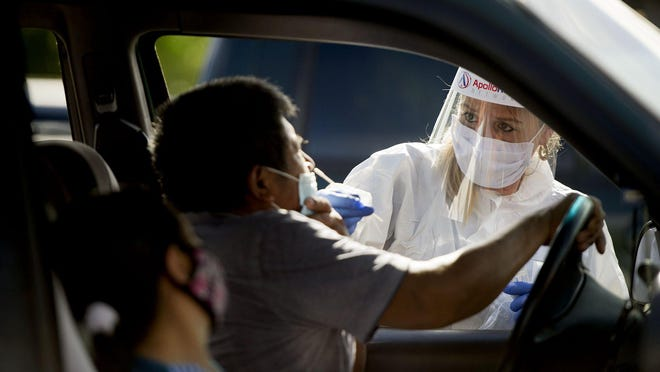 Volunteer phlebotomist Rachel Soto collects  a nasal swab to test for COVID-19 from a motorists at Harold Grimes Memorial Park in Lake Worth Saturday July 18, 2020.