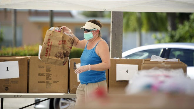 Joanne Linden helps deliver school supplies to vehicles during the annual Back 2 School Extravaganza event outside Lake Park Town Hall Saturday. The Saturday event was drive-through only due to COVID-19.