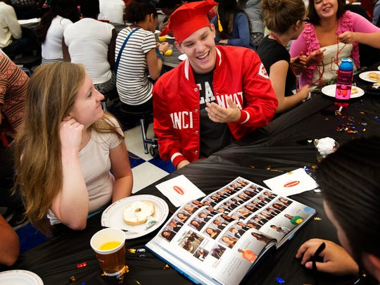 South Fort Myers High School students, Christian Enriquez, 18, center, and Melissa Stewart, 18, socialize while looking at the yearbook during senior breakfast. This year, students can download an app that features videos and slideshows.
