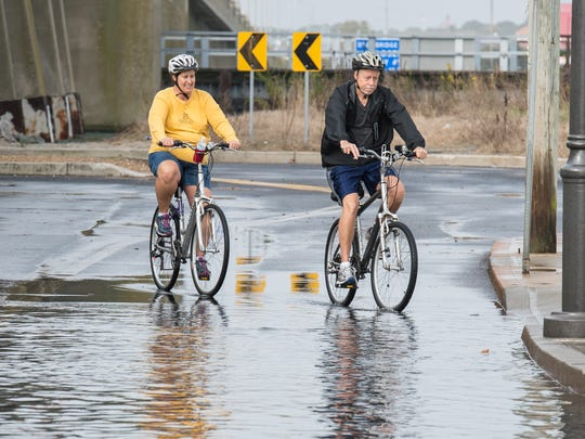 Two cyclists circumnavigate a flooded section of North Division Street and Saint Louis Avenue in Ocean City on Sunday, Nov. 5, 2017. Many roads in Ocean City were partially flooded due to the King Tide.