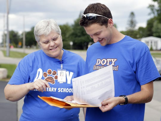 Sharon Rychter, fifth-grade bilingual teacher, and Bryant Scherer, first-grade bilingual teacher, plan their route before walking door-to-door Wednesday to distribute informational door hangers to Doty Elementary students and their families about the start of the school year.