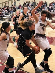 Cloudcroft's Marisol Paulik, center, brings a ball through the lane.