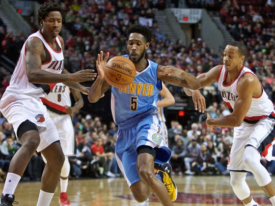 Denver Nuggets forward Will Barton, center, loses control of the ball while dribbling past Portland Trail Blazers center Ed Davis, left, and guard C.J. McCollum, right, during the first half of an NBA basketball game in Portland, Ore., Wednesday, Dec. 30, 2015.