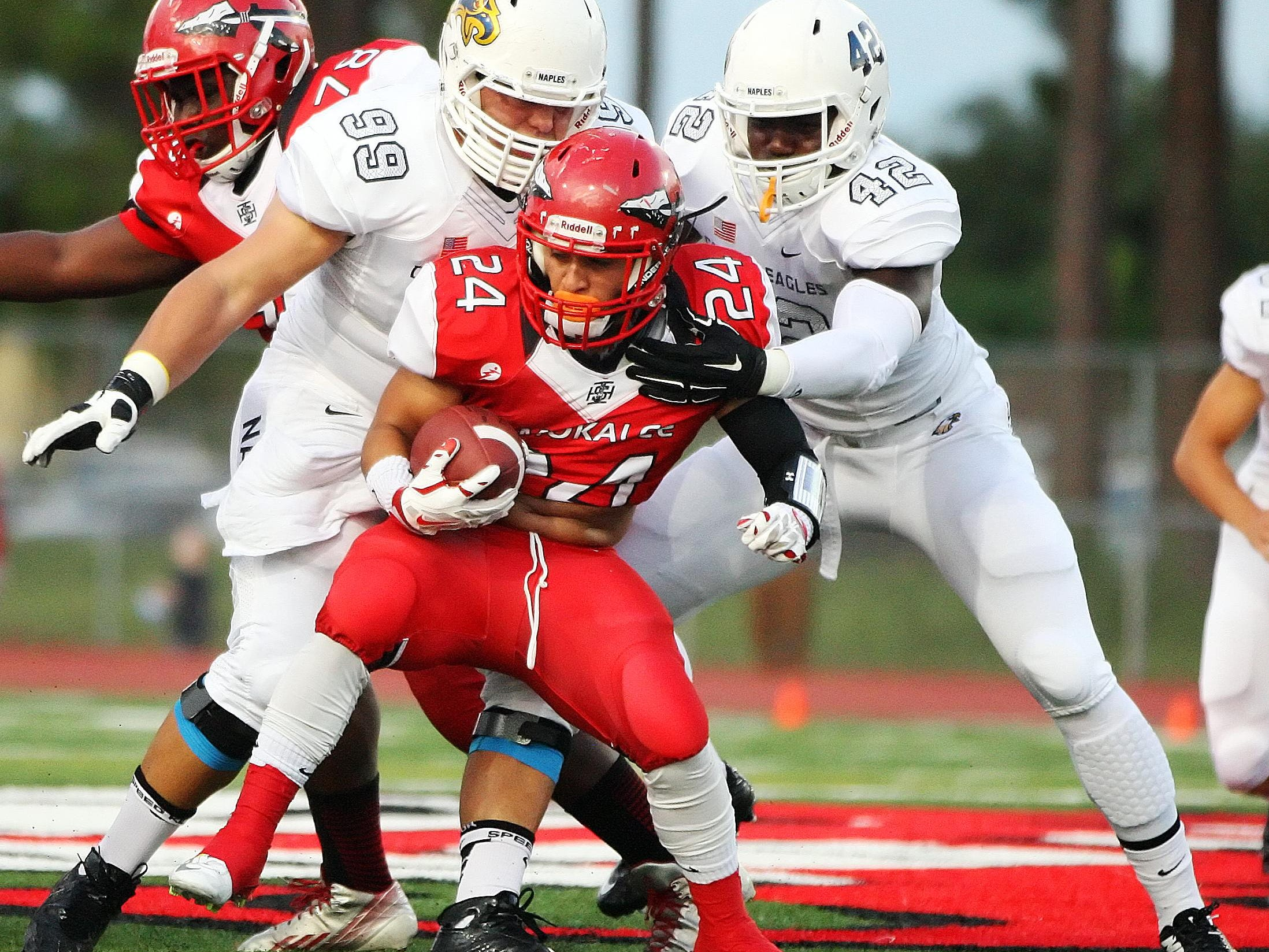 Naples High School defenders Crandall Maines, left, and Wycleff Phanor tackle Immokalee's John Garza on Friday at Immokalee High School. Naples beat Immokalee 63-7.