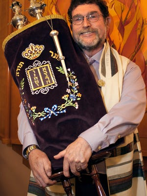 Rabbi Larry Karol of Temple Beth-El poses for a photo with a Torah scroll, the holiest book within Judaism, made up of the five books of Moses, in front of the synagogue's Ark in December 2015.