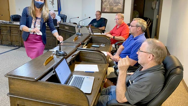 At Tuesday evening's special Crookston City Council meeting, Liza Donabauer, management consultant with DDA Human Resources, Inc., collects paper ballots from council members and the mayor on which they picked their preferred city administrator candidates to invite to Crookston for interviews. Seated left to right are Mayor Dale Stainbrook and council members Clayton Briggs, Steve Erickson, Jake Fee and Bobby Baird.