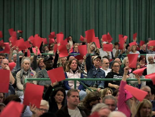 Constituents and community members raise red cards