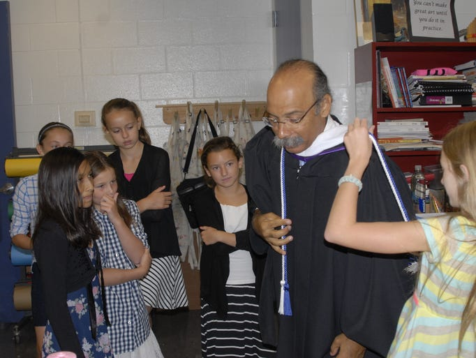 Celie Hudson of Indian Hill and Terrace Park helps her sixth-grade advisor, art teacher Ully Marin of Milford, adjust the cords on his robe before the Opening Convocation. Watching, from left: front, Jasmine Gonzales of Symmes Township, Sophia O'Brien of Indian Hill and Abby Blum of Springfield Township; back, Sabrina DelBello and Rowan Castrucci, both of Indian Hill.