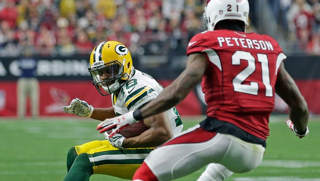 Green Bay Packers wide receiver Randall Cobb looks to make a move after catching a pass as Arizona Cardinals cornerback Patrick Peterson defends at University of Phoenix Stadium.