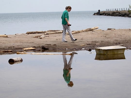 Irondequoit resident, Karin Nowicki, looks over the garbage standing water at the Small Beach at Irondequoit Bay State Marine Park after high lake waters flooded area beaches.