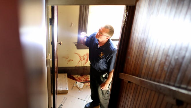 Crime scene investigator Tim Gormly examines the entryway into the apartment of Quandavier Hicks on Chase Avenue in Northside in June 2015.