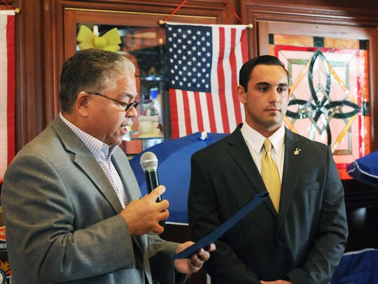 Nelson Eddy Rivera, left, director of Dutchess County Veterans' Services, presents former Army Sgt. Marc Coviello, right, with a commendation from the County Executive's office at a fundraiser event at Rambler's Rest in Poughquag on April 19, 2015.