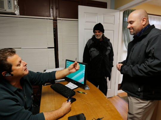 Jonathan Kovac's new landlord, Dave Green, hands his apartment keys to Gregg Pieples of Greater Cincinnati Behavioral Health Services.