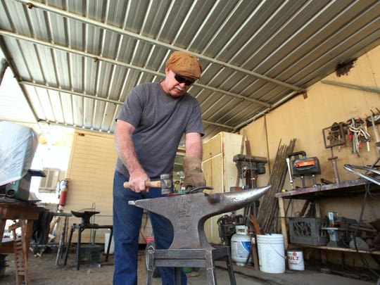 Sculptor Tolley Marney works on a horseshoe at the Smoke Tree Stables on Tuesday, January 13, 2015 in Palm Springs, Calif.