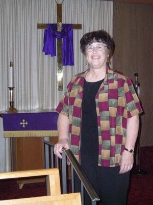 Rev. Mary McQueen, pastor of First Community Congregational United Church of Christ at the stairs of the altar of the church.