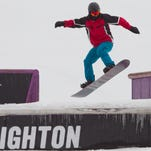 A snowboarder navigates a jump on the snowboard course.