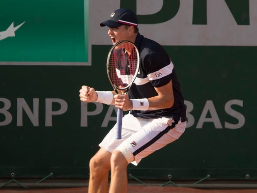 American John Isner celebrates a point during his five-set