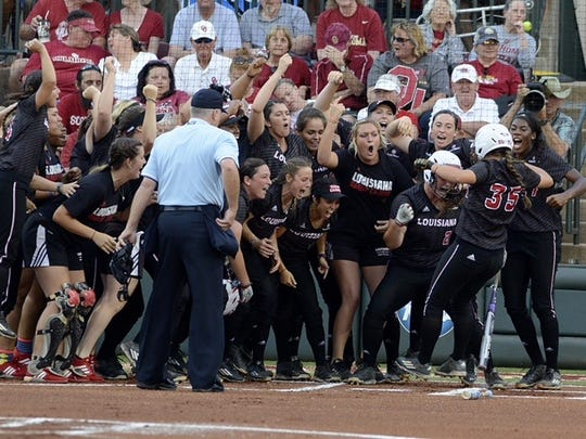 The Cajuns celebrate as Haley Hayden crosses home plate after a home run Thursday against Oklahoma in the NCAA Super Regionals.
