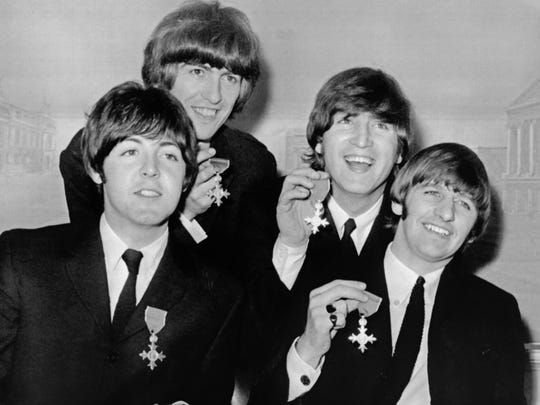 The Beatles (from Left), Paul McCartney, George Harrison, John Lennon and Ringo Starr hold up their MBE (Bristish Empire Medal) awards at news conference following their investiture on October 26, 1965 at Buckingham Palace in London.