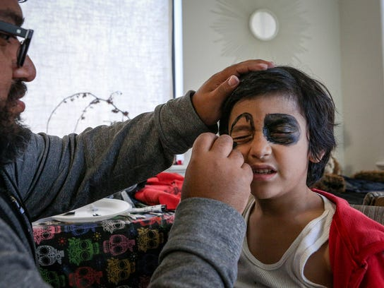 James Estrada applying make-up to his son Joh at their home in Salt Lake City on Monday, Nov. 6, 2017.