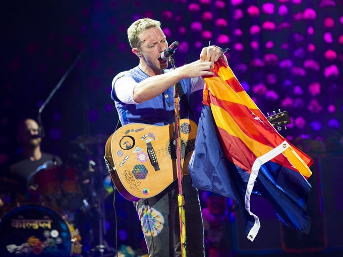Coldplay lead singer Chris Martin unfurls an Arizona