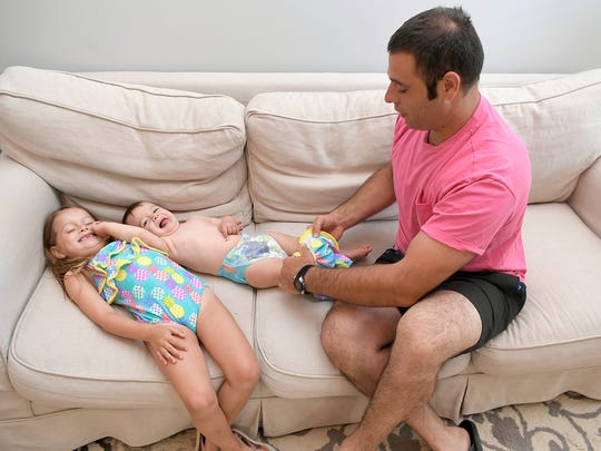Eric Andonian gets his daughters ready for the pool.