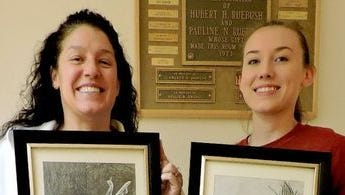 Deming High students Dakota Hughes, right, donated framed paper drawings to CHANCES Treasurer Angie Jenkins for the art auction.