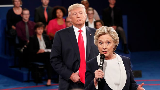 Democratic presidential nominee Hillary Clinton, right, speaks as Republican presidential nominee Donald Trump listens during the second presidential debate at Washington University in St. Louis on Oct. 9. 2016.