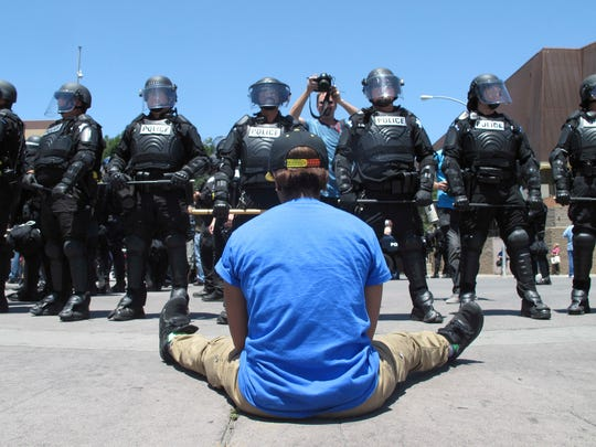 A woman sitting in the street talks with riot police after a campaign rally for Republican presidential candidate Donald Trump in Fresno, Calif., on Friday, May 27, 2016. The crowd beat drums, chanted anti-Trump slogans and marched around the arena in downtown Fresno. Officers arrested two other people after the rally on suspicion of unlawful assembly after they did not follow orders to clear the streets.