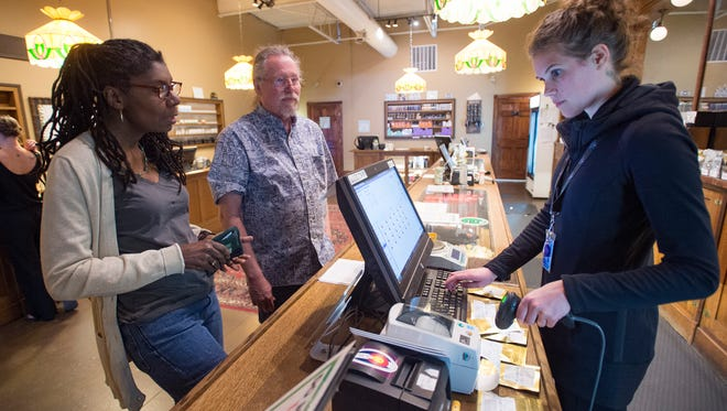 Janie and David Johansen, visiting from Texas, pay for their purchase with Melissa Schiau, bud tender, at Organic Alternatives on Wednesday.