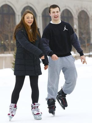 Shayna Raasch, 16, left, and Derek Reiche, 18, both of Weston, ice skate at The 400 Block in downtown Wausau.