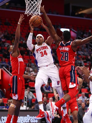 Pistons forward Tobias Harris tries to get off a first half shot between Wizards guard Bradley Beal and Wizards center Ian Mahinmi during the Pistons' 122-112 loss on Friday, Jan. 19, 2018, at Little Caesars Arena.