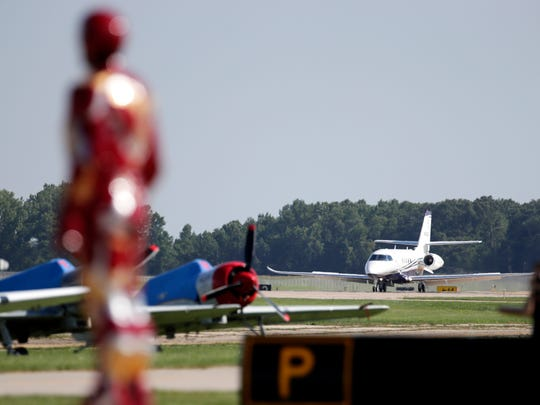 Iron Man waits for Stan Lee's plane to come to a stop during the afternoon airshow at EAA AirVenture 2017 Thursday, July 27, 2017, at Wittman Regional Airport in Oshkosh, Wis.