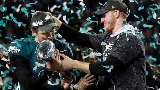 Eagles quarterback Carson Wentz, right, hands the Vince Lombardi trophy to Nick Foles after winning Super Bowl LII against the New England Patriots, Sunday, Feb. 4, 2018, in Minneapolis. The Eagles won 41-33.