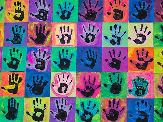 Some handprint art is on display Sunday at the Art for Charlie event at the Marriott Hotel in East Lansing.
