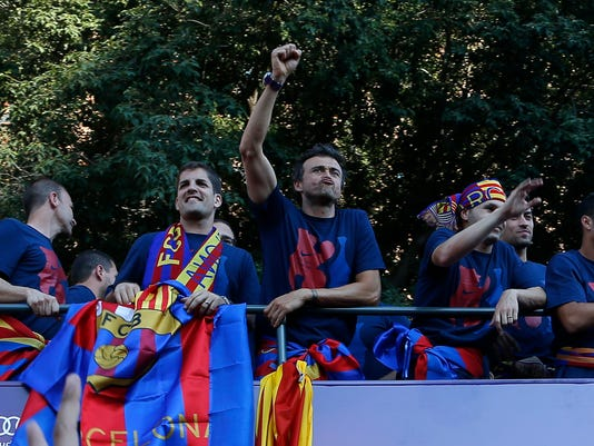 Barcelona's coach Luis Enrique centre, waves from the team bus during celebrations in Barcelona, Spain Sunday June 7, 2015 after winning the Champions League final soccer match Saturday by beating Juventus Turin 3-1. Barcelona won the triple this season winning the Spanish League title, the Copa del Rey and the Champions League. (AP Photo/Emilio Morenatti)