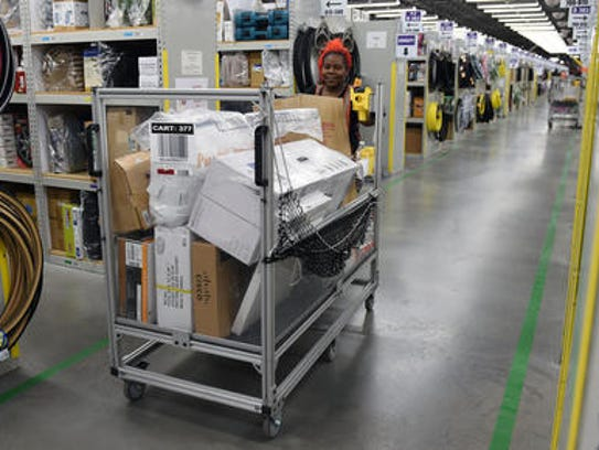 Amazon employee Angela Daniels fulfills customer orders at the company's Wilson County warehouse on Sept. 20, 2015.