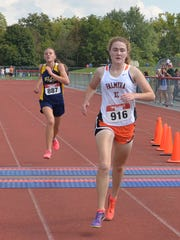 Palmyra's Sarah Hollen crosses the finish line just ahead of Elco's Lily Brubaker to win the girls race at the Lebanon County Cross Country Championships on Saturday at Annville-Cleona.