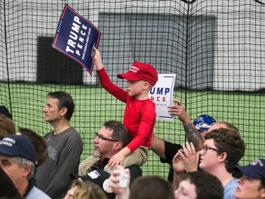 A young Trump supporter holds up a campaign sign during
