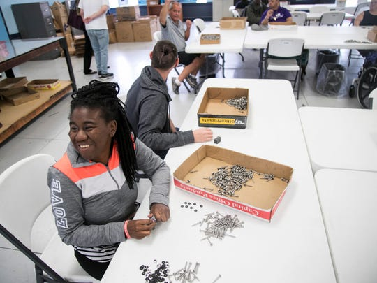 LARC clients Brittany McCoy and Steven King work on adding washers to screws as part of their jobs at LARC in Fort Myers.