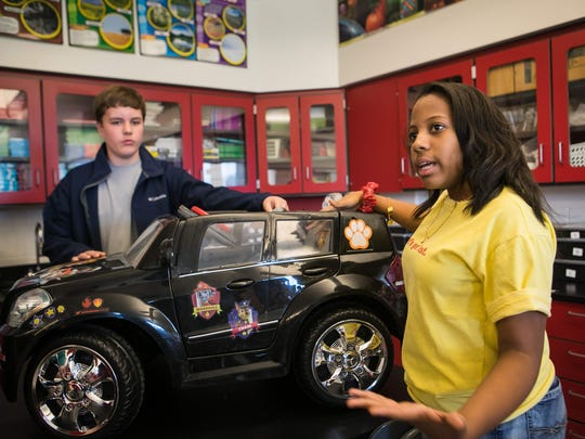 Eighth graders Elise Sampson (right) and Nichlos Crawford at Smyrna Middle school talk about the work they are doing designing and modifying 6 and 12-volt battery-operated cars with adaptable gears, programming, switches and safety supports, specifically tailored for children to meet their mobility potential.