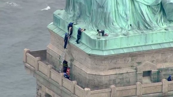 """This still image taken from video Courtesy of PIX11 News in New York, shows police talking to a woman who climbed to the base of the Statue of Liberty in New York on July 4, 2018.  According to media reports, Liberty Island has been evacuated and ferries to the site have been halted, while law enforcement attempt to get the woman down from the statue.  / AFP PHOTO / PIX11 News / HO / RESTRICTED TO EDITORIAL USE - MANDATORY CREDIT """"AFP PHOTO / Courtesy of PIX11 News"""" - NO MARKETING NO ADVERTISING CAMPAIGNS - DISTRIBUTED AS A SERVICE TO CLIENTSHO/AFP/Getty Images ORIG FILE ID: AFP_1763EF"""