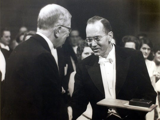 Charles Townes, on right, receives the Nobel Prize in a vintage photo on display as part of a display honoring Townes at Furman.