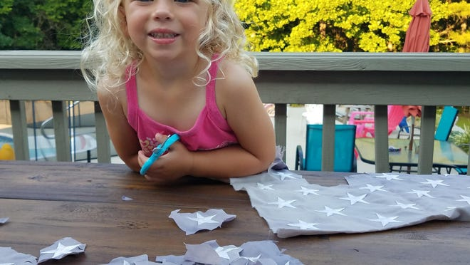 "Pictured, four year-old Bella Bennett recently cut out just over two hundred stars to be glued on to cards for veterans. Her grandfather, Ralph F. Iorio Jr. of River Bend is a member of B.P.O.E. Lodge No. 764. For years, his family has helped collect old worn-out American flags to re-purpose the stars. The cards are given to veterans to thank them for their service and let them know they are never forgotten. Bella decided she wanted to help and grabbed a pair of scissors. Bella also loves giving the completed cards out to veterans. She shakes their hands and says ""Thank you for your service"". Bella is the daughter of Michelle Iorio-Bennett and James Bennett of New Bern."