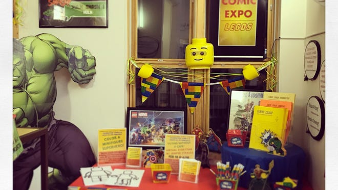 Tables are set up in the lobby of the library where patrons can grab their own LEGO pencils and pads of paper, sign or draw in the guest book and pick up a mini figure to color themselves. Courtesy photo