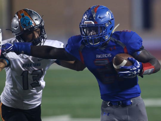 Then-Americas running back Josh Fields, right, fends off a tackle attempt by Pebble Hills defender Jaylien Spires during a football game last year at the SAC.