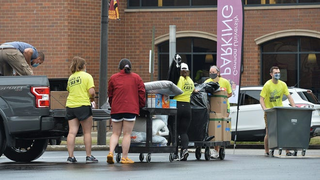 With everyone wearing face masks, Gannon University's move-in crew volunteers deliver student belongings to dormitory rooms on Aug. 4. Officials have a COVID-19 testing plan in place and since then, four students have tested positive.