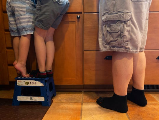 Craig Stodola's two young sons share a stool so they