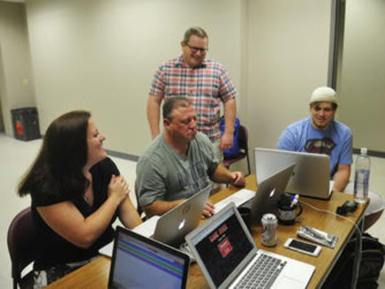 Robin Burton, left, Rick Aites, center, instructor Steve Brownlee, standing, Tanner Terry and Caitlin Stein, far right, work in their small group writing code for a video game at Nashville Software School on Sept. 9.